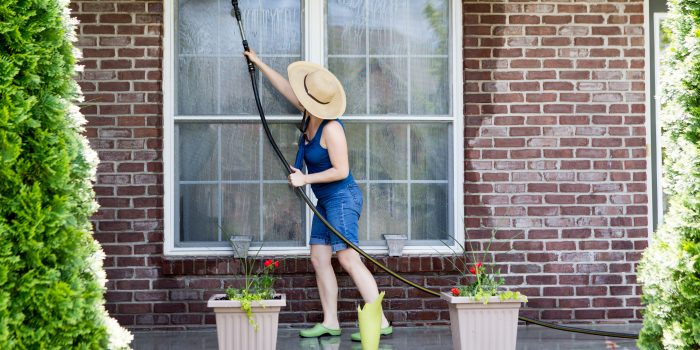 Housewife standing on a patio washing the windows of her house with a hose attachment as she spring-cleans the exterior at the start of the new spring season